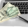 Money with magnifying glass on laptop close-up — Stock Photo #19733443