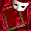 White mask and empty frame on red silk fabric — Stock Photo