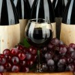 Composition of wine bottles, glass and  grape,on wooden barrel, close up — Stock Photo