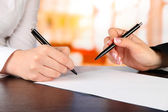 Two business partners signing document, on bright background — Stock Photo