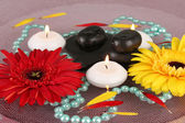 Spa stones with flowers and candles in water on plate — ストック写真