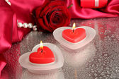 Beautiful candles, rose and red silk on grey wet background — Stock Photo