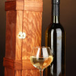 Wooden case with wine bottle on wooden table on brown background — Stock Photo
