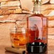 Bottle and Glass of whiskey and cigar on brick wall background — Stock Photo