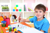 Cute little boy painting in his notebook — Stock Photo