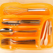 Orange plastic cutlery tray with checked cutlery and wooden spoons on wooden table - Stock Photo
