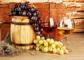 Composition of wine,box and grapes on wooden barrel on table on brick wall background — Stok fotoğraf