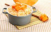 Taste rice porridge with pumpkin in saucepan on tablecloth background — Stock Photo