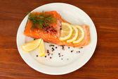 Fresh salmon fillet with herbals and lemon slices on plate,on wooden background — Stock Photo