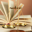 Gold scales of justice and books on brown background — Stock Photo #19894033