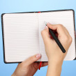 Stock Photo: Hand write on notebook, on color background