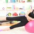 Young woman doing fitness exercises with gym ball at home - ストック写真
