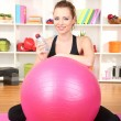 Young woman with gym ball at home - ストック写真