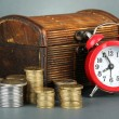 Alarm clock with coins in chest on grey background — Stok fotoğraf
