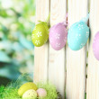 Art Easter background with eggs hanging on fence — Foto de Stock