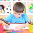 Stock Photo: Cute little boy drawing in his album
