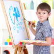 Little boy painting paints picture on easel — Stock Photo #19896217