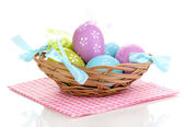 Colorful easter eggs in basket on napkin isolated on white — Stock Photo