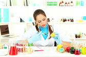 Young female scientist injecting GMO into lemon in laboratory — Stock Photo