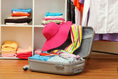 Open silver suitcase with clothing in room — Foto de Stock