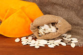 Pumpkin seeds in sack, on wooden background — Stock Photo