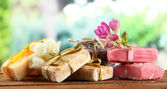 Natural handmade soap, on wooden table, on green background — Stock Photo