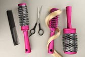 Comb brushes, hair and cutting shears, on grey background — Stock Photo