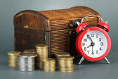 Alarm clock with coins in chest on grey background — Stock Photo