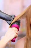 Beautiful woman and hands with hairdryer in beauty salon — Stock Photo