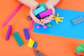 Child's hands holding plasticine over desk — Stock Photo