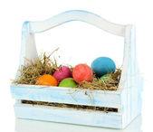 Uova di pasqua nel paniere in legno isolato su bianco — Foto Stock