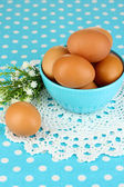 Eggs in bowl on blue tablecloth close-up — Stock Photo