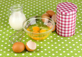 Broken egg in bowl and various ingredients next to them on green tablecloth close-up — Stock Photo