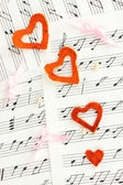 Decorative hearts from dry orange peel on musical notes — Stock Photo
