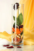 Dried rose in glass vase on white-yellow fabric background — Stock Photo