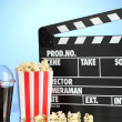 Movie clapperboard, cola and popcorn on blue background — Zdjęcie stockowe