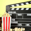 Movie clapperboard, cola and popcorn on background — Stock Photo #19999805