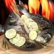 Two fish dorado with lemon on pan on wooden table on fire background — Stock Photo
