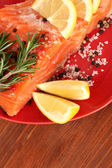 Fresh salmon fillet with herbals and lemon slices on plate, close up — Stock Photo