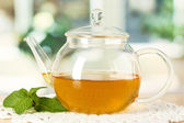 Teapot with mint on table in room — Stockfoto
