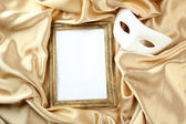 White mask and empty frame on golden silk fabric — Stock Photo