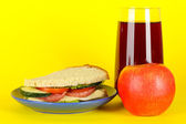 Sandwich on plate with apple and juice on yellow background — Stock Photo