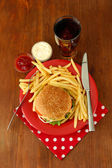 Tasty cheeseburger with fried potatoes and cold drink, on wooden background — Stock Photo