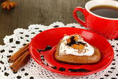 Chocolate cookie in form of heart with cup of coffee on wooden table close-up — Stock Photo