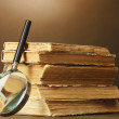 Stock Photo: Magnifying glass and books on brown background