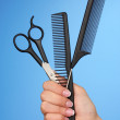 Color combs and scissors in female hand on color background — Stock Photo