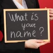 Young woman holding sign What is your name? — Stock Photo