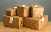 Parcels boxes with kraft paper, on wooden table on grey background — Stock Photo