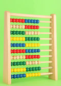 Bright wooden toy abacus, on green background — Stock Photo