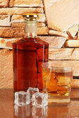 Bottle and Glass of whiskey and ice on brick wall background — Stock Photo